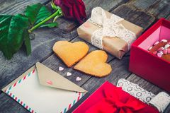 Festive composition with homemade cookies in shape of heart, rose flower, gift box. card with envelope, vintage ribbon. Gift for l. Over on Valentine`s day Royalty Free Stock Photography