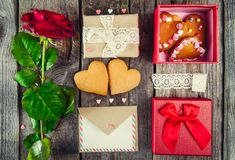 Festive composition with homemade cookies in shape of heart, rose flower, gift box. card with envelope, vintage ribbon. Gift for l. Over on Valentine`s day Stock Photo