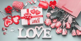 Festive composition of love for Valentines day made with gift box and red bow, shopping bag and roses, hearts and party. Accessories. With Love message. Flat royalty free stock photography
