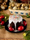 Festive composition made of Easter cake kulich and red coloured quail eggs. Festive composition made of Easter cake kulich, red coloured quail eggs and spring Royalty Free Stock Photos