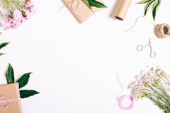 Festive composition on white table: carnation flowers, gifts, ri. Bbons, wrapping paper. Top view, copy space Stock Photos