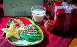 Festive  cookie plate for Santa Clause. Festive cookie  plate for Santa Clause, with decorated sugar cookies, cold milk and a gift too Royalty Free Stock Image