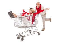 Festive couple messing about in shopping trolley Stock Images