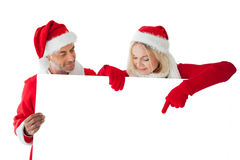 Festive couple pointing to large white card Stock Images