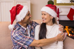 Festive couple in santa hat hugging on the couch Stock Images