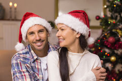 Festive couple in santa hat hugging on the couch Stock Image