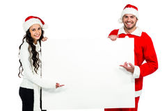 Festive couple showing a poster Royalty Free Stock Images