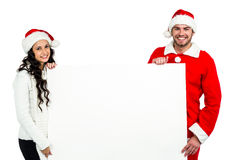 Festive couple showing a poster Royalty Free Stock Image