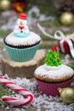 Festive cupcake with  Christmas tree and snowman. Two festive cupcake with  Christmas tree and snowman Stock Images