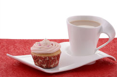 Festive cupcake with tea on fancy plate. And red placemat Stock Images