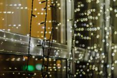 Festive dark blurred background with bokeh lights, electric garland and house. stock images