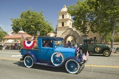 Festive decorated antique automobile makes its way down main street during a Fourth of July parade in Ojai, CA Royalty Free Stock Photography