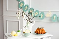 Festive decoration of the Easter table, a vase with a branch and decorations from flowers and eggs, biscuits with rabbit stock photos