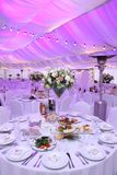 Festive decoration of the hall with flowers, table setting. In the tent royalty free stock photos