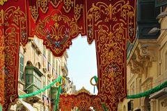 Festive decoration of the streets of the capital of Malta, Valletta, on the day of a religious holiday. Magnificent scenery of gold-embroidered fabric in honor royalty free stock images