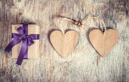 Festive decoration for Valentine`s Day. Two wooden hearts and a gift box with a bow on a wooden background. Royalty Free Stock Photo