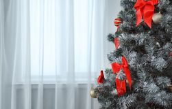 Festive decorations on Christmas tree in stylish living interior stock images