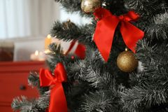 Festive decorations on Christmas tree in stylish living room royalty free stock photography