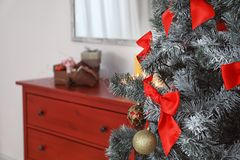 Festive decorations on Christmas tree in stylish room interior royalty free stock images