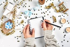 Festive decorations, delicate wavy ribbons, metallic star shaped confetti and notebook with wish list on white table. Flat lay style. Planning concept royalty free stock photo