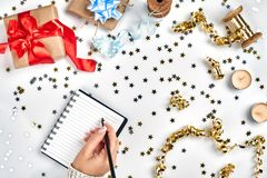 Festive decorations, delicate wavy ribbons, metallic star shaped confetti and notebook with wish list on white table stock images