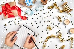 Festive decorations, delicate wavy ribbons, metallic star shaped confetti and notebook with wish list on white table royalty free stock photography