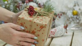 Festive decorations. The work of a designer-decorator. On the eve of Christmas. Transfer new year gift. Women`s hands send a Christmas gift into the hands of stock video footage