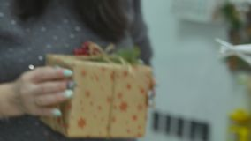 Festive decorations. The work of a designer-decorator. On the eve of Christmas. Transfer new year gift. Women`s hands send a Christmas gift into the hands of stock footage