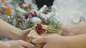 Festive decorations. The work of a designer-decorator. On the eve of Christmas. Transfer new year gift. Women`s hands send a Christmas gift into the hands of stock video