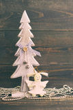 Festive decorative Christmas tree and a toy angel on a wooden background in vintage color. Royalty Free Stock Images