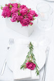 Festive dining table setting with pink roses. White tablecloths and napkins, candles, holiday dinner Royalty Free Stock Images
