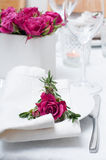 Festive dining table setting with pink roses. White tablecloths and napkins, candles, holiday dinner Royalty Free Stock Photo