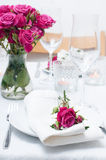 Festive dining table setting with pink roses. White tablecloths and napkins, candles, holiday dinner Royalty Free Stock Image