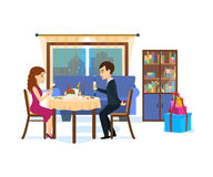 Festive dinner of couple, against background of evening city. A loving couple amidst the home furnishings in the living room at a festive dinner, against the Royalty Free Stock Photos