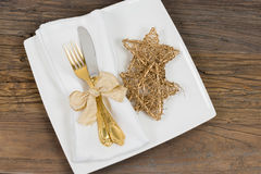 Festive dinner table setting. Festive dinner table setting with gold cutlery and stars on rustic wooden table Stock Photos