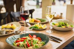 Festive dinner with tasty salads, fish dishes and glass of wine. Healthy food in cafe stock images