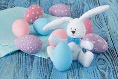 Festive easter eggs on blue table with toy bunny Stock Photography