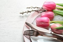 Festive Easter table setting with flowers on wooden background, above view. royalty free stock image