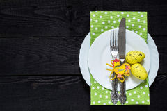 Festive Easter table setting. Plates, knife and fork with ribbon, chicken and egg Royalty Free Stock Photo
