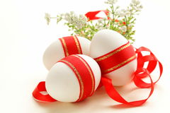 Festive eggs decorated with red ribbon - symbol of Easter Stock Photography