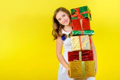 Beautiful girl in a festive dress holds a lot of gifts and smiles royalty free stock photography