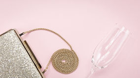 Festive evening golden clutch and champagne glass on pink. Holid. Ay and celebration background. Luxury accessories and party concept. Horizontal, wide screen Stock Images
