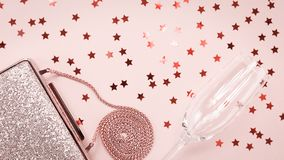 Festive evening golden clutch and champagne glass with star sprinkles on pink. Holiday and celebration background. Luxury royalty free stock image