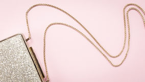Festive evening golden clutch on pink. Holiday and celebration b Stock Image