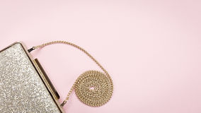 Festive evening golden clutch on pink. Holiday and celebration b Royalty Free Stock Photo