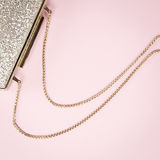 Festive evening golden clutch on pink. Holiday and celebration b Stock Photos