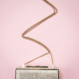 Festive evening golden clutch on pink. Holiday and celebration b Royalty Free Stock Image