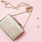 Festive evening golden clutch with star sprinkles on pink. Holid Royalty Free Stock Photography