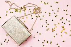 Festive evening golden clutch with star sprinkles on pink. Holid Stock Photo