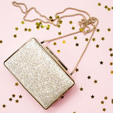 Festive evening golden clutch with star sprinkles on pink. Holid Stock Images